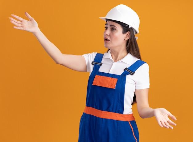 Mylić patrząc na bok młoda kobieta budowniczy w mundurze, rozkładając ręce na białym tle na pomarańczowej ścianie