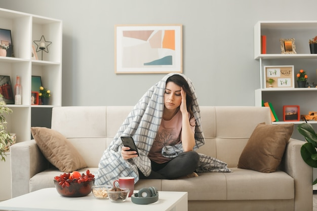 Myśląc kładąc dłoń na świątyni młoda dziewczyna owinięta w kratę trzymająca i patrząca na telefon siedzący na kanapie za stolikiem kawowym w salonie