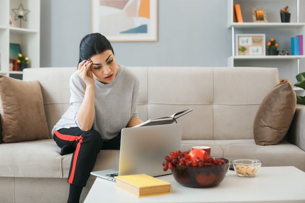 Myśląc, kładąc rękę na czole, młoda dziewczyna używała laptopa, trzymając notebooka siedzącego na kanapie za stolikiem kawowym w salonie