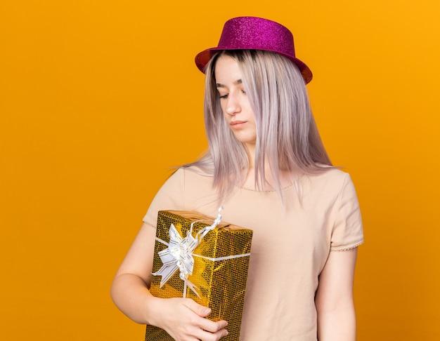 Myśląc młoda piękna dziewczyna w kapeluszu imprezowym, trzymająca i patrząca na pudełko upominkowe