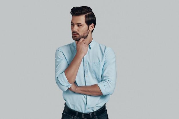 Myśląc o… przystojny młody mężczyzna odwracający wzrok i trzymający rękę na brodzie, stojąc na szarym tle