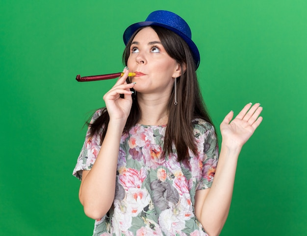 Myśląc, patrząc w górę, młoda piękna dziewczyna w kapeluszu imprezowym dmuchająca punkty gwizdka ręką z boku na zielonej ścianie