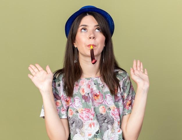 Myśląc, patrząc w górę, młoda piękna kobieta w kapeluszu imprezowym wieje gwizdek, rozkładając ręce na oliwkowozielonej ścianie