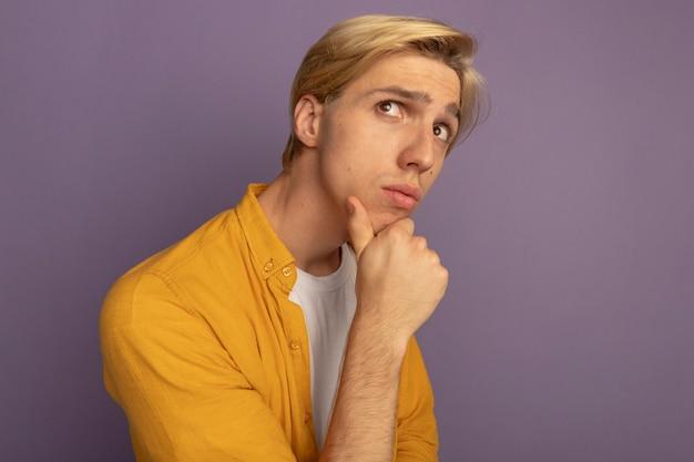 Myśląc, patrząc w górę, młody blondyn w żółtej koszulce chwycił podbródek