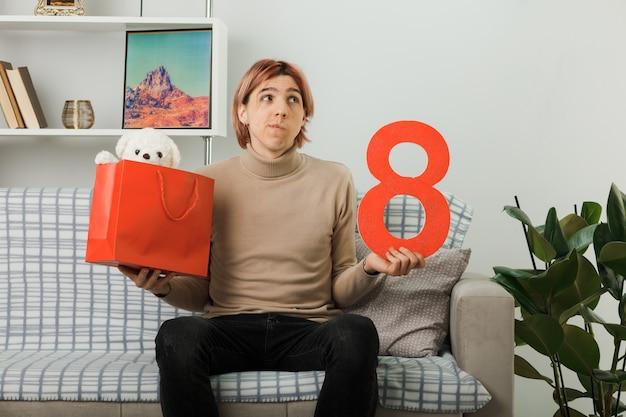 Myśląc patrząc w górę przystojnego faceta na szczęśliwy dzień kobiet trzymający numer osiem z torbą na prezenty siedzącą na kanapie w salonie