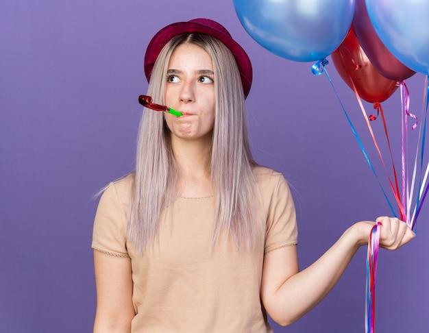 Myśląc patrząc z boku młoda piękna dziewczyna w kapeluszu imprezowym trzymająca balony dmuchający gwizdek