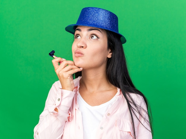 Myśląc patrząc z boku młoda piękna dziewczyna w kapeluszu imprezowym, trzymająca gwizdek na imprezę