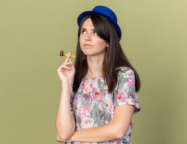 Myśląc patrząc z boku młoda piękna kobieta w kapeluszu imprezowym trzymająca gwizdek na tle oliwkowej ściany