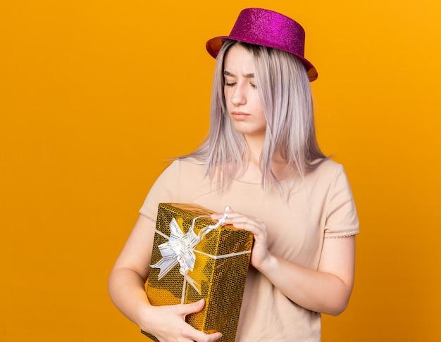 Myśląc z zamkniętymi oczami młoda piękna dziewczyna w kapeluszu imprezowym trzymająca pudełko na prezent