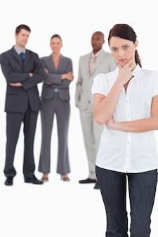 Myśląca bizneswoman z trzy kolegami za ona