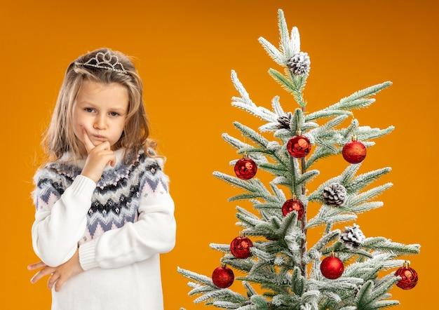 Myśląca dziewczynka stojąca w pobliżu choinki ubrana w tiarę z girlandą na szyi kładąc dłoń na brodzie na białym tle na pomarańczowym tle