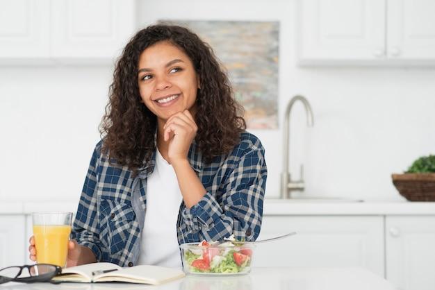Myśląca kobieta trzyma szklankę soku