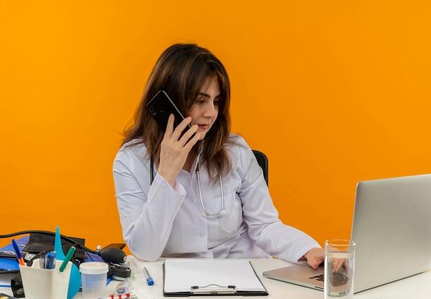 Myśląca kobieta w średnim wieku ubrana w szlafrok medyczny ze stetoskopem siedząca przy biurku praca na laptopie z narzędziami medycznymi mówi przez telefon i używany laptop na izolowanym pomarańczowym tle z miejscem na kopię