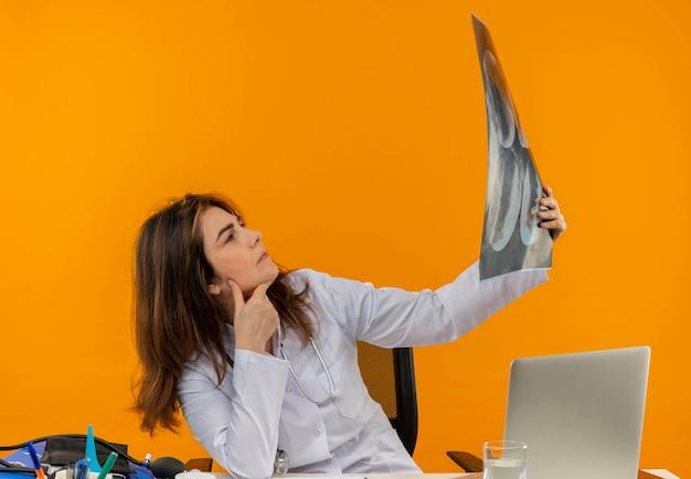 Myśląca kobieta w średnim wieku ubrana w szlafrok medyczny ze stetoskopem siedząca przy biurku praca na laptopie z narzędziami medycznymi trzymająca i patrząc na prześwietlenie na odizolowanym pomarańczowym tle z miejscem na kopię