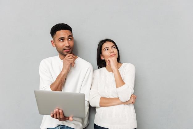 Myśląca kochająca para stoi nad szarości ścianą używać laptop