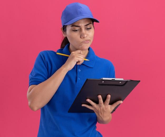 Myśląca młoda dostawcza dziewczyna ubrana w mundur z czapką trzymająca i patrząca na schowek, kładąc rękę na brodzie na różowej ścianie