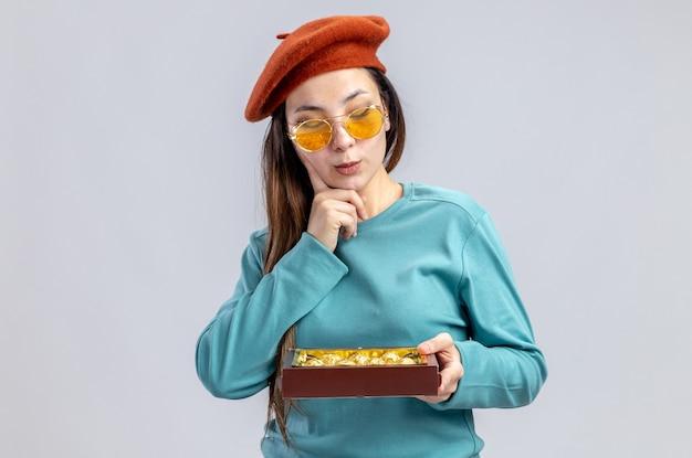 Myśląca młoda dziewczyna na walentynki w kapeluszu w okularach, trzymająca i patrząca na pudełko cukierków na białym tle
