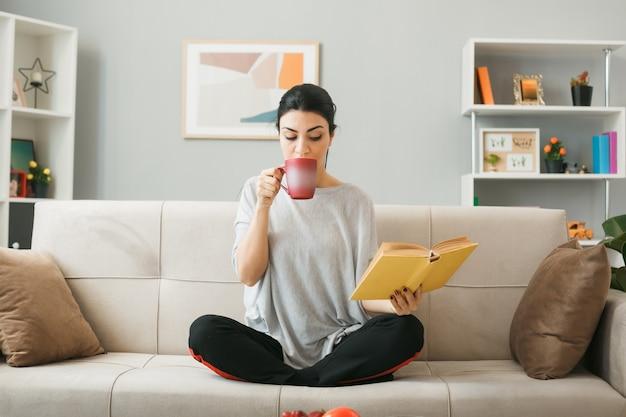 Myśląca młoda dziewczyna trzyma filiżankę herbaty, czytając książkę w dłoni, siedząc na kanapie za stolikiem kawowym w salonie