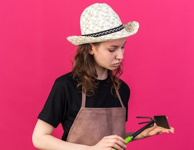 Myśląca młoda kobieta ogrodniczka w kapeluszu ogrodniczym, trzymająca i patrząca na grabie motyki odizolowana na różowej ścianie