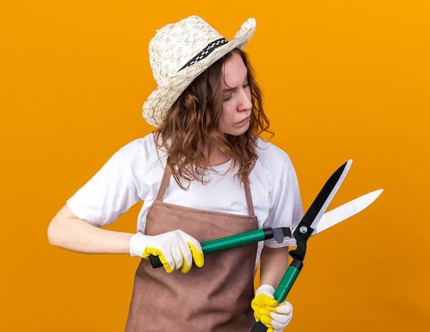 Myśląca młoda kobieta ogrodniczka w kapeluszu ogrodniczym z rękawiczkami trzymająca i patrząca na sekator