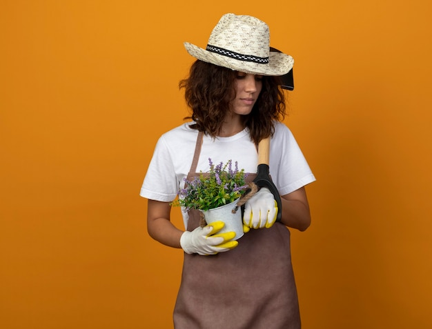 Myśląca młoda kobieta ogrodniczka w mundurze na sobie kapelusz ogrodniczy i rękawiczki, trzymając kwiat w doniczce i kładąc łopatę na ramieniu