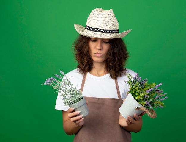Myśląca młoda kobieta ogrodniczka w mundurze na sobie kapelusz ogrodniczy, trzymając i patrząc na kwiaty w doniczkach