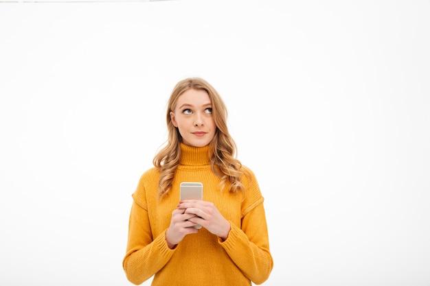 Myśląca młoda kobieta używa telefon komórkowego.