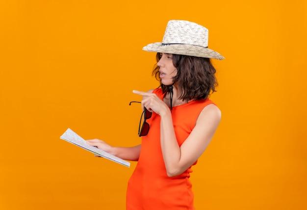 Myśląca młoda kobieta z krótkimi włosami w pomarańczowej koszuli na sobie kapelusz przeciwsłoneczny, trzymając mapę z okularami przeciwsłonecznymi
