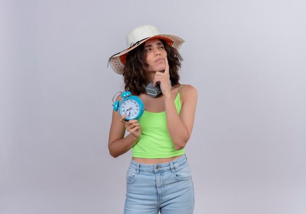 Myśląca młoda kobieta z krótkimi włosami w zielonym topie w kapeluszu przeciwsłonecznym, trzymając palec wskazujący na brodzie, trzymając niebieski budzik na białym tle