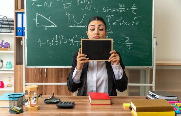 Myśląca młoda nauczycielka siedzi przy stole z przyborami szkolnymi, trzymając i patrząc na mini tablicę w klasie