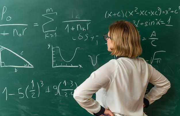 Myśląca młoda nauczycielka stojąca przed tablicą, kładąc ręce na biodrze w klasie