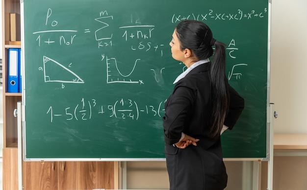 Myśląca młoda nauczycielka stojąca przed tablicą, kładąca rękę na biodrze w klasie