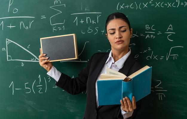 Myśląca młoda nauczycielka stojąca przed tablicą trzymająca mini tablicę patrząca na książkę w ręku w klasie