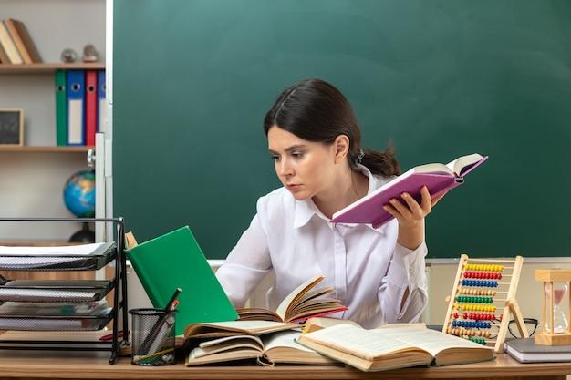 Myśląca młoda nauczycielka trzymająca i czytająca książkę siedząca przy stole z narzędziami szkolnymi w klasie