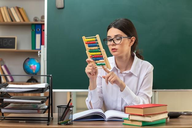 Myśląca młoda nauczycielka w okularach, trzymająca i patrząca na liczydło, siedząca przy stole z szkolnymi narzędziami w klasie