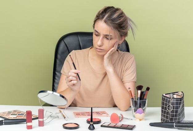 Myśląca młoda piękna dziewczyna siedzi przy biurku z narzędziami do makijażu, trzymając i patrząc na pędzel do makijażu, kładąc rękę na policzku na białym tle oliwkowo-zielonym