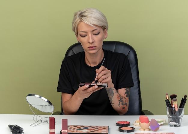 Myśląca młoda piękna dziewczyna siedzi przy stole z narzędziami do makijażu, trzymając i patrząc na paletę cieni do powiek odizolowaną na oliwkowym tle