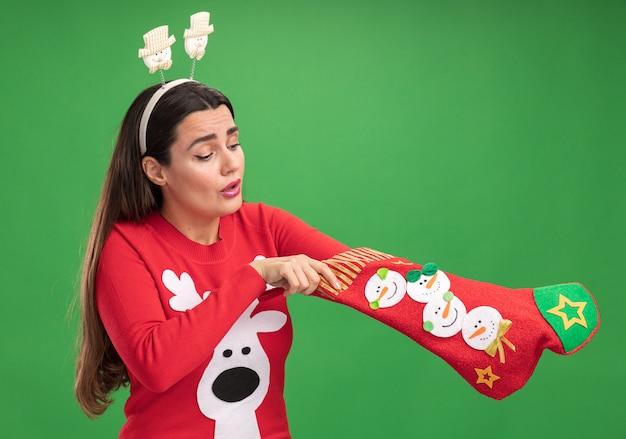 Myśląca młoda piękna dziewczyna ubrana w świąteczny sweter z świątecznym obręczem do włosów wkładanie ręki w świąteczne skarpetki na białym tle na zielonym tle