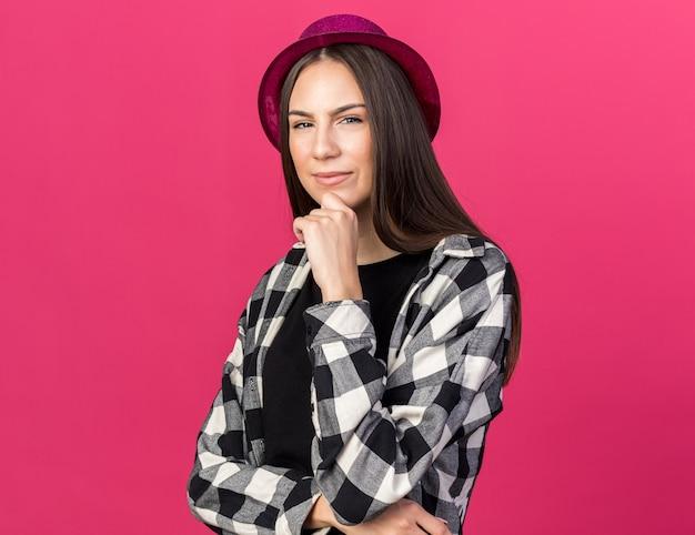 Myśląca młoda piękna dziewczyna w imprezowym kapeluszu chwyciła podbródek odizolowana na różowej ścianie
