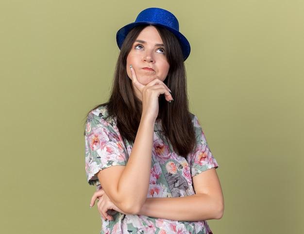 Myśląca młoda piękna dziewczyna w imprezowym kapeluszu, kładąc rękę na podbródku