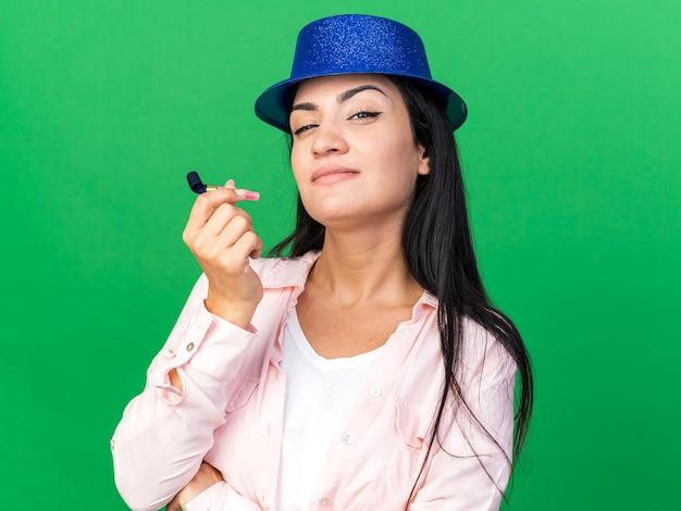 Myśląca młoda piękna dziewczyna w kapeluszu imprezowym trzymająca gwizdek na imprezę