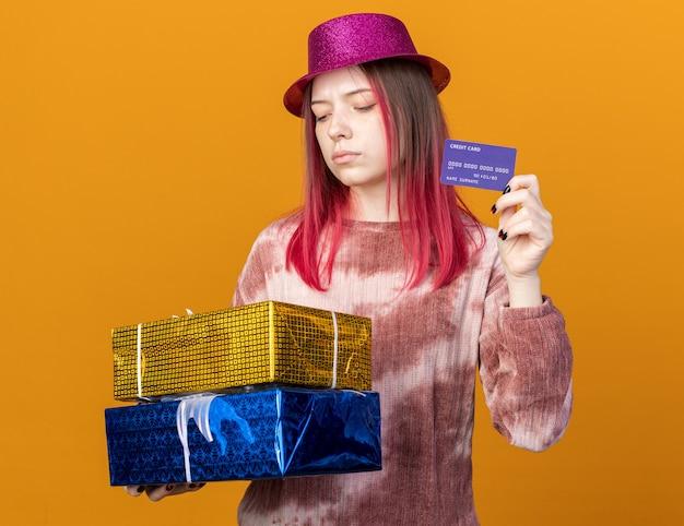 Myśląca młoda piękna dziewczyna w kapeluszu imprezowym trzymająca pudełka na prezenty z kartą kredytową