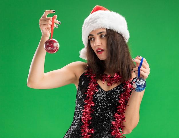 Myśląca młoda piękna dziewczyna w świątecznym kapeluszu z girlandą na szyi, trzymająca i patrząca na bombki choinkowe odizolowane na zielonym tle