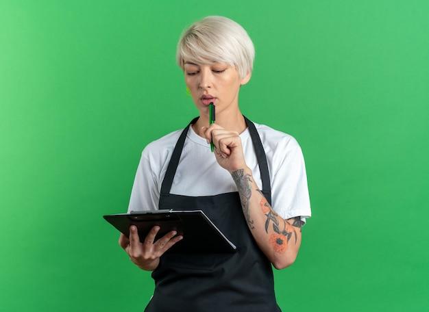 Myśląca młoda piękna kobieta fryzjerka w mundurze trzymająca i patrząca na schowek, kładąc pióro na brodzie na białym tle na zielonym tle