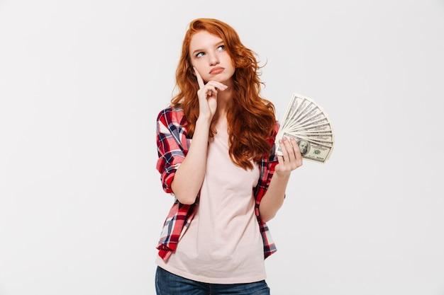 Myśląca młoda rudzielec dama trzyma pieniądze.