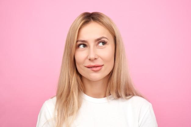 Myśląca osoba w białej koszuli, rozmarzona dziewczyna myśli i patrząc w górę na różowym tle