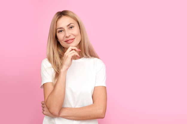 Myśląca osoba w białej koszuli, trzymając podbródek, marzycielska dziewczyna myśli i patrząc na aparat odizolowany na różowo