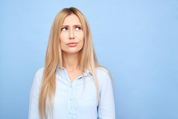 Myśląca osoba w koszuli biznesowej, marzycielska dziewczyna myśli i patrząc w górę na białym tle na niebiesko