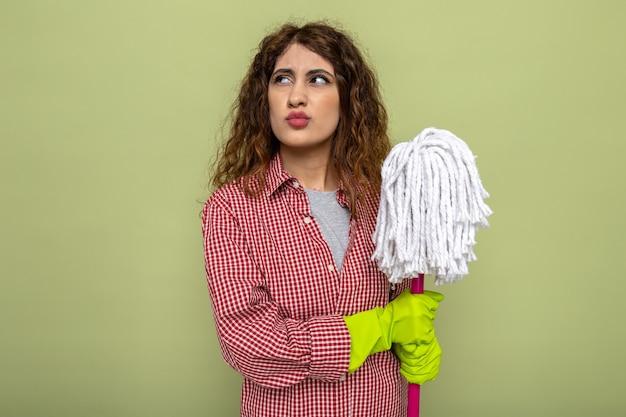 Myśląca patrząc z boku młoda sprzątaczka w rękawiczkach trzymająca mopa odizolowana na oliwkowozielonej ścianie