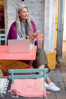 Myśląca starsza pani z siwymi włosami trzyma telefon komórkowy siedzący przy stole z laptopem